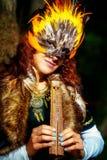 Muchacha con la máscara shamanic de la pluma y vestido histórico en los alrededores del arbolado que tocan la flauta ornamental d Imagenes de archivo