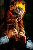 Muchacha con la máscara shamanic de la pluma y vestido histórico en los alrededores del arbolado que tocan la flauta ornamental d Foto de archivo libre de regalías