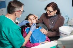 Muchacha con la madre en la primera visita dental Dentista pediátrico que hace el primer chequeo para el paciente en la oficina d Imagenes de archivo