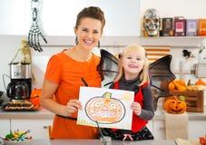 Muchacha con la madre que muestra el dibujo de la Jack-O-linterna de Halloween Fotos de archivo