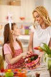 Muchacha con la madre que prepara la cesta de Pascua con los huevos Foto de archivo