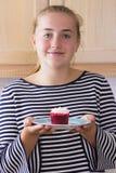 Muchacha con la magdalena en cocina Fotografía de archivo libre de regalías