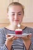 Muchacha con la magdalena en cocina Imagen de archivo