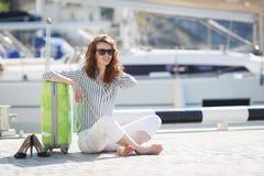 Muchacha con la maleta en el embarcadero cerca del yate Fotografía de archivo libre de regalías