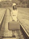 Muchacha con la maleta en los ferrocarriles Imagen de archivo libre de regalías