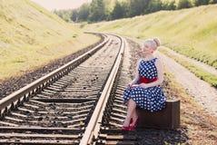 Muchacha con la maleta en los ferrocarriles Imagenes de archivo