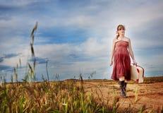 Muchacha con la maleta que camina abajo de una trayectoria al aire libre. felicidad. Imagenes de archivo