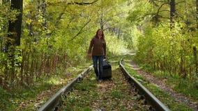 Muchacha con la maleta que camina a lo largo del ferrocarril almacen de video