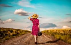 Muchacha con la maleta que despierta en el camino rural fotos de archivo