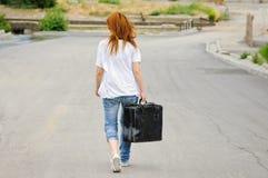 Muchacha con la maleta que recorre abajo de la calle Imágenes de archivo libres de regalías