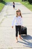 Muchacha con la maleta que sale de la hermana Imagen de archivo libre de regalías