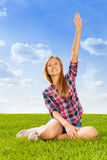 Muchacha con la mano para arriba en el aire que se sienta en hierba verde Imagen de archivo libre de regalías