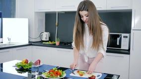 Muchacha con la manzana del corte del cuchillo en la tajadera para la ensalada vegetal en el fondo de la cocina metrajes