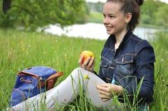 Muchacha con la manzana en una comida campestre Imágenes de archivo libres de regalías