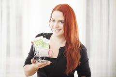 Muchacha con la mini carretilla del carro de la compra con el billete de banco euro Imagenes de archivo