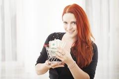 Muchacha con la mini carretilla del carro de la compra y billete de banco del dólar Imagen de archivo libre de regalías
