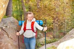 Muchacha con la mochila que camina a través de una montaña Fotografía de archivo