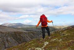 Muchacha con la mochila que se coloca encima de una montaña y que mira Imágenes de archivo libres de regalías