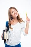 Muchacha con la mochila que sostiene los libros y el lápiz Foto de archivo libre de regalías