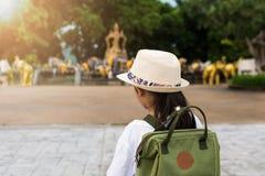 Muchacha con la mochila que ve a una estatua santa en el cabo del promthep Imagen de archivo libre de regalías