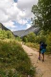 Muchacha con la mochila y bastones que dan un paseo abajo de una montaña Imagen de archivo libre de regalías