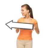 Muchacha con la muestra de la flecha de la dirección Fotos de archivo libres de regalías