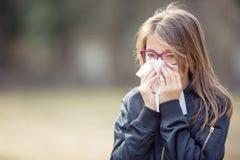 Muchacha con la nariz que sopla del síntoma de la alergia Muchacha adolescente que usa un tejido en un parque Fotos de archivo libres de regalías