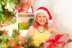 Muchacha con la opinión de los regalos de Navidad a través del árbol de NY Imagen de archivo libre de regalías