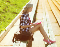 Muchacha con la PC de la tableta que trabaja en el parque de la ciudad Fotografía de archivo