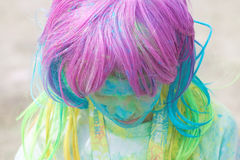 Muchacha con la peluca colorida cubierta con el polvo del color que mira abajo Foto de archivo libre de regalías