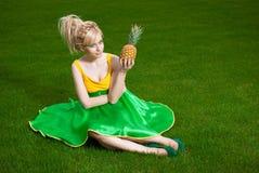 Muchacha con la piña que se sienta en césped Imagen de archivo