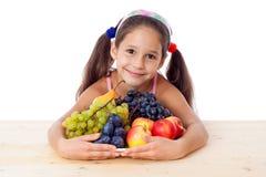 Muchacha con la pila de fruta Foto de archivo libre de regalías
