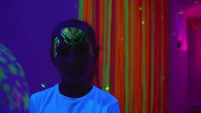 Muchacha con la pintura del cuerpo en la cara que sostiene el globo en sitio oscuro con la luz del fluor almacen de video
