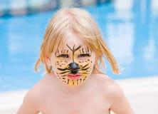 Muchacha con la pintura en su cara en la piscina Imágenes de archivo libres de regalías