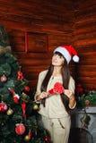 Muchacha con la piruleta y el árbol de navidad Imagen de archivo libre de regalías