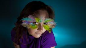 Muchacha con la pluma colorida en su cara imagenes de archivo