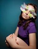 Muchacha con la pluma colorida en su cara imagen de archivo libre de regalías