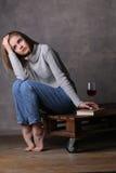 Muchacha con la presentación del libro y del vidrio de vino Fondo gris Fotos de archivo libres de regalías