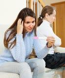 Muchacha con la prueba de embarazo contra madre madura infeliz Fotos de archivo libres de regalías