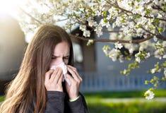 Muchacha con la reacción alérgica en árbol floreciente Fotos de archivo
