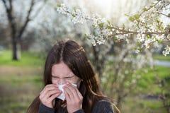 Muchacha con la reacción alérgica en árbol floreciente Imagenes de archivo