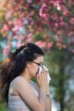 Muchacha con la reacción alérgica en árbol floreciente Imagen de archivo libre de regalías