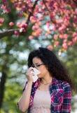Muchacha con la reacción alérgica en árbol floreciente Foto de archivo