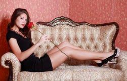 Muchacha con la rosa del rojo en el sofá del vintage Imágenes de archivo libres de regalías