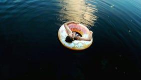 Muchacha con la rueda de agua en el lago en la tarde fotos de archivo