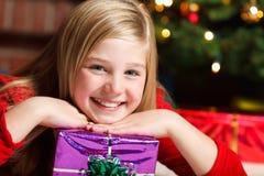 Muchacha con la sonrisa del regalo de la Navidad Imágenes de archivo libres de regalías