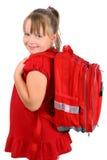 Muchacha con la sonrisa roja del bolso de escuela aislada en blanco Imagen de archivo libre de regalías