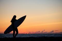 muchacha con la tabla hawaiana en puesta del sol en la playa Imágenes de archivo libres de regalías