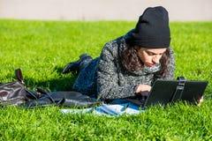 Muchacha con la tableta, mintiendo en hierba verde Foto de archivo