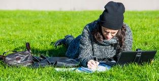 Muchacha con la tableta, mintiendo en hierba verde y la escritura Imagen de archivo libre de regalías
